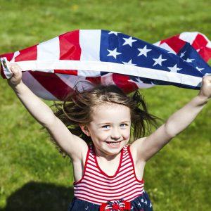 Patriotic holiday  child with American flag running.