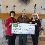 Kathy J and Teri M present a check to David W, a recent WCCU winner