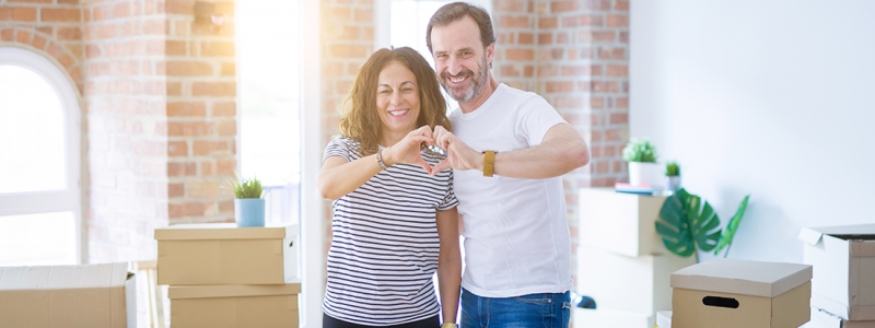 Middle age senior couple moving to a new home with boxes around smiling in love showing heart symbol and shape with hands. Romantic concept.